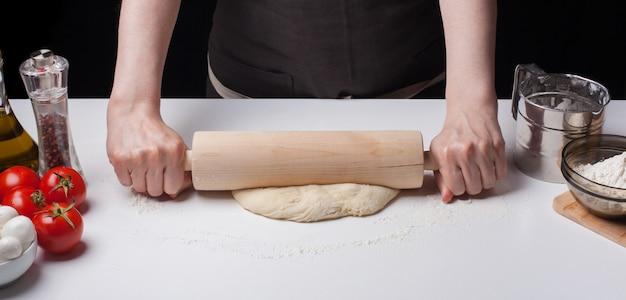 女性の手はピザ生地をロールバックしました。