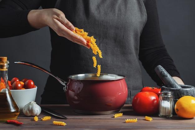台所の鍋でイタリアのパスタを調理します。