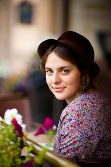 カメラを見て、笑みを浮かべてカフェに座ってお茶のカップと帽子の美しい若い女性。