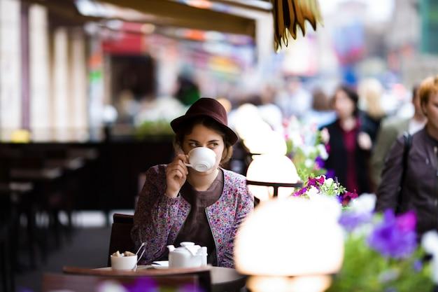 カフェに座ってお茶を一杯で美しい女性。