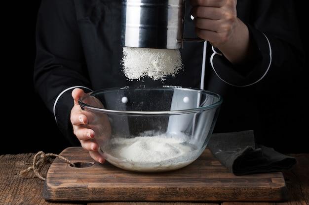 シェフの手が生の生地に小麦粉の粉を注ぐ。