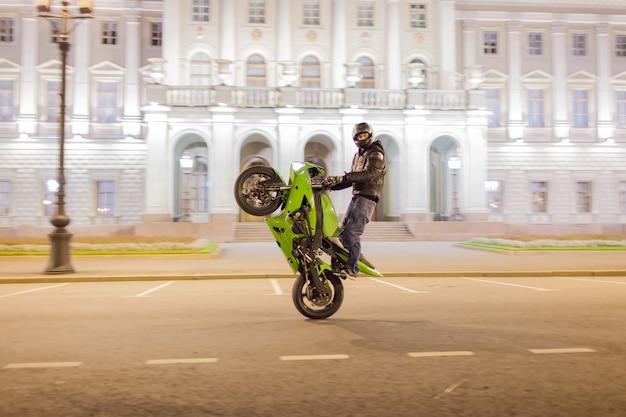 男性のモーターサイクリストはあなたの彼のスポーツのオートバイに夜を漂流しました。