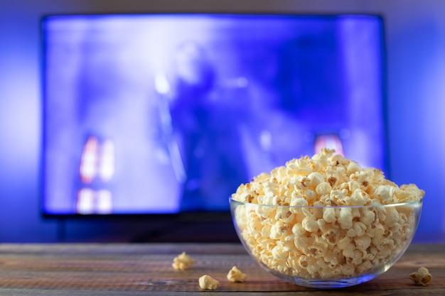 Стеклянная миска с попкорном и рабочим телевизором.