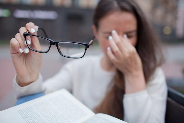 手で眼鏡を持つ女性のクローズアップの肖像画。