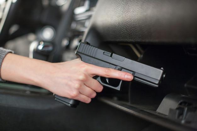 Рука вытаскивает пистолет из бардачка.
