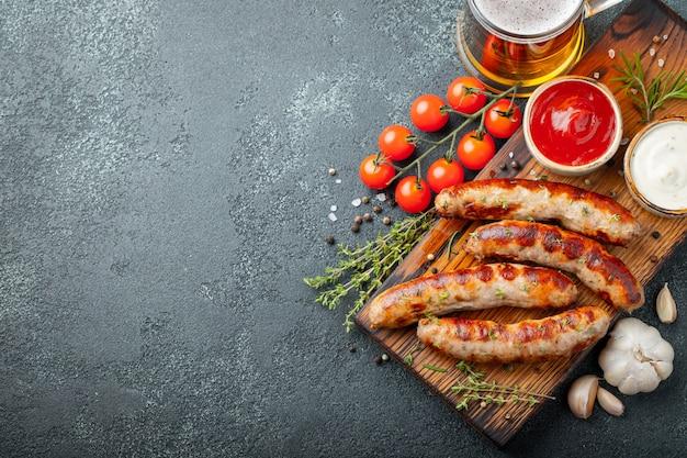 Жареные колбаски с соусами и зеленью.