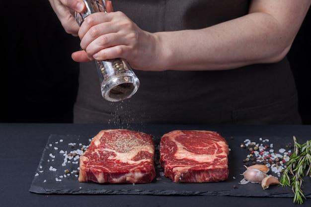 女性シェフがビーフステーキを用意しています。