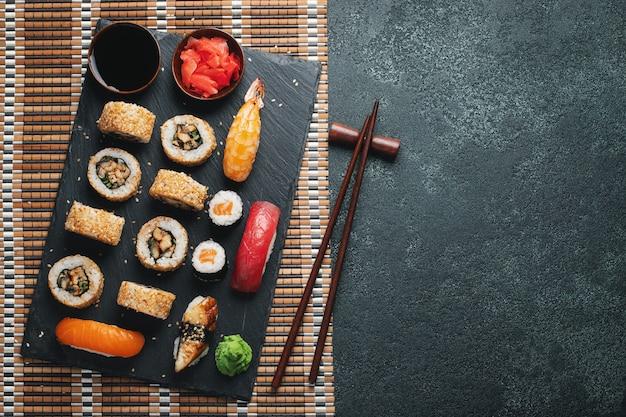 暗い石のテーブルの上に寿司とマキのセット。コピースペース平面図。平置き。