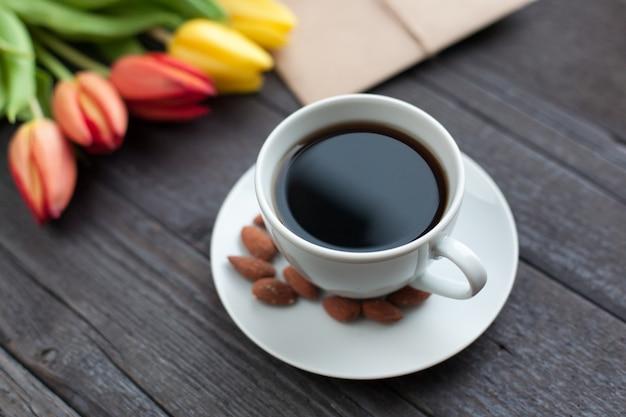 黄色とオレンジ色のチューリップとコーヒーの白いカップ。