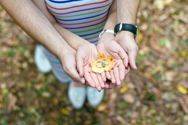 若いカップルは公園を歩いています、素敵なカップルは庭を歩いています