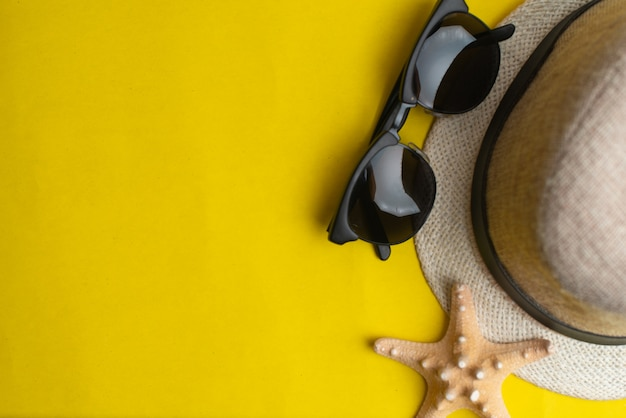 黄色の背景に夏のアクセサリー、シェル、帽子、サングラス。夏と海のコンセプトです。