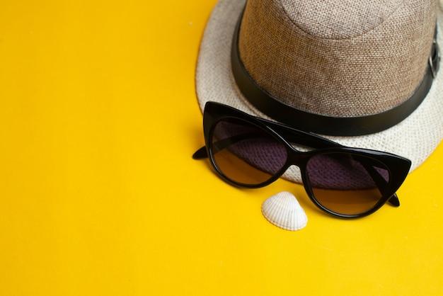 夏用アクセサリー、貝殻、帽子、サングラス。夏休みと海のコンセプト。