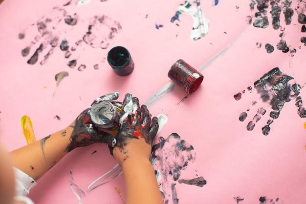 Руки картины мальчика с акварелями на розовом бумажном листе. маленький мальчик с кистью и красками.