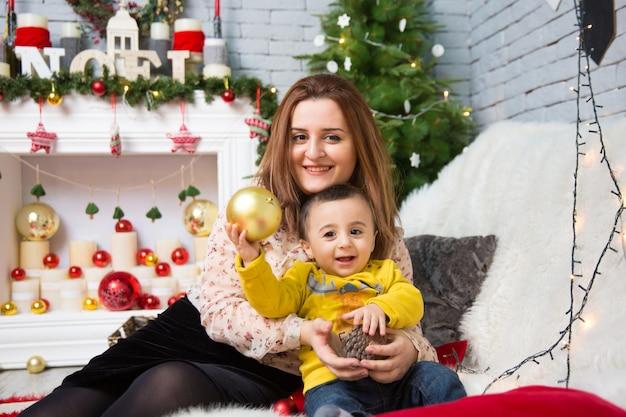 幸せな母と男の子のメリークリスマスの肖像画は、クリスマスを祝います。
