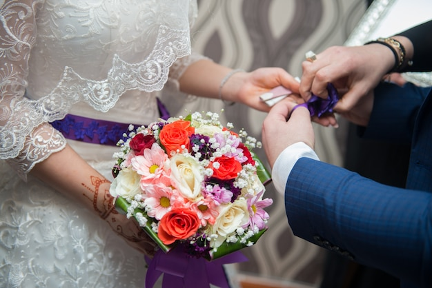結婚式の日。新郎と新婦の花を持つ。幸せなカップル