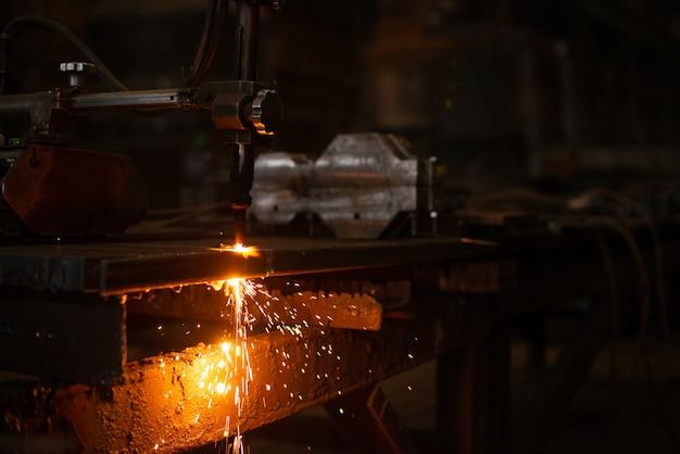 Плита из листового металла с искрящимся светом. чпу лазерная резка металла, современные промышленные технологии. изготовление готовых деталей.