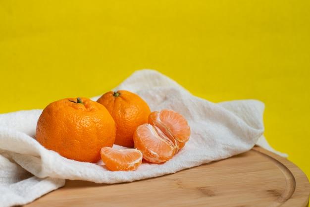 Мандарин и кусочки цитрусовых на желтом фоне. апельсин, мандарин или мандарин натуральные фрукты.