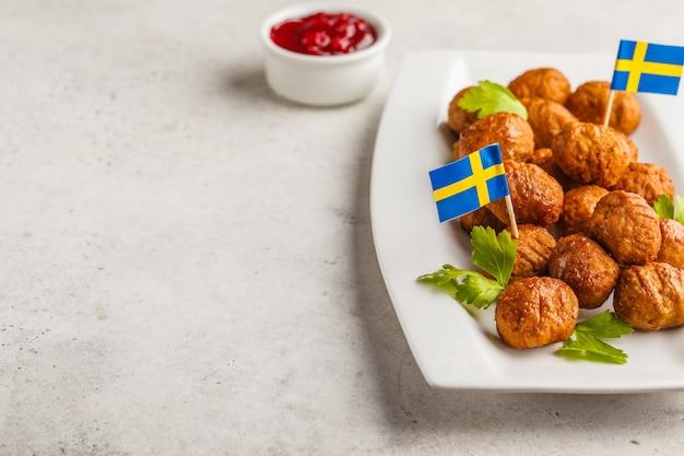 白いプレートにスウェーデンの伝統的なミートボール。スウェーデン料理のコンセプトです。