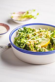 Кале, киноа, авокадо веганский салат в миску белого на белом фоне.