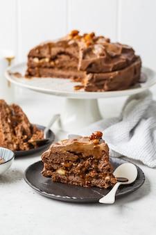 自家製のスニッカーズケーキチョコレートクリームとキャラメルの黒い受け皿、白い背景の上の作品。