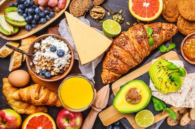 暗い背景に健康的なバランスの取れた朝食。ミューズリー、牛乳、ジュース、クロワッサン、チーズ、ビスケット。