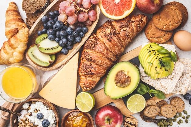 白い背景の上の健康的なバランスの取れた朝食。ミューズリー、ジュース、クロワッサン、チーズ、ビスケット、フルーツ、上面図。