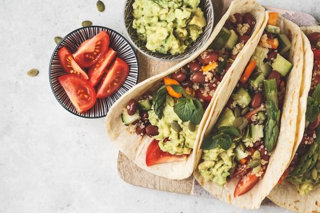 キノア、アスパラガス、豆、野菜、ワカモレのビーガントルティーヤ。