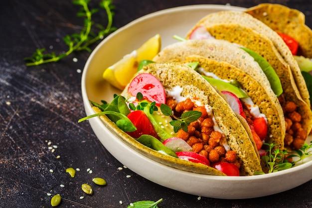 焼きひよこ豆、アボカド、ソースと野菜のビーガンタコス。