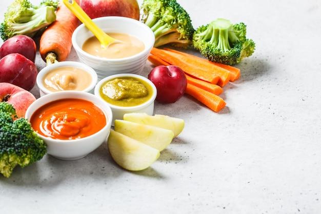 食材を使った白いボールの野菜と果物の赤ちゃんのピューレ。