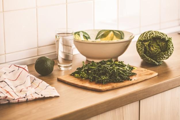 キッチンでケールとアボカドのグリーンサラダを調理