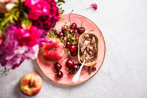 花、チョコレートデザート、ピンクのプレートの果実。