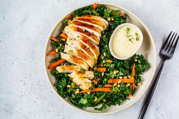 Салат из куриной грудки на гриле с капустой, кедровыми орешками и соусом цезарь в белой тарелке.