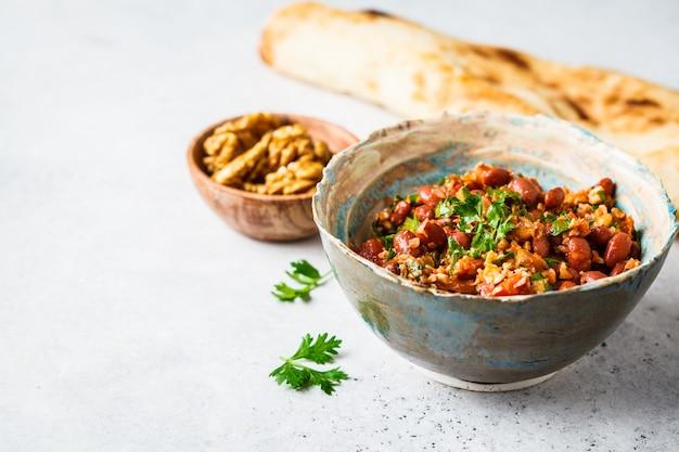 白灰色のテーブルの上のボウルにグルジアの伝統的な豆ロビオ。