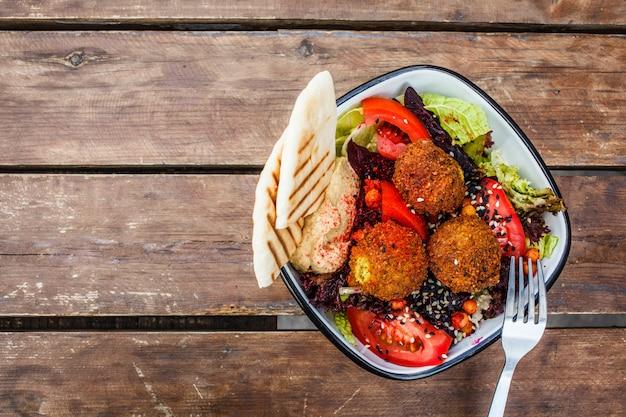 木製のテーブル、トップビューでボウルにフムス、ビーツと野菜のファラフェルサラダ。