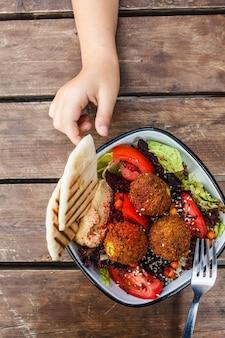 イスラエルの屋台。木製のテーブル、トップビューでボウルにフムス、ビーツと野菜のファラフェルサラダ。