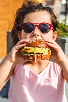 Маленькая девочка ест гамбургер на улице.