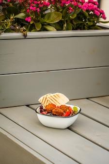 Израильская уличная еда. салат из фалафеля с хумусом, свеклой и овощами в миске в ресторане.