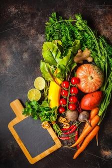 秋野菜のテーブル。カボチャ、ズッキーニ、サツマイモ、ニンジン、ビートの暗いテーブル。