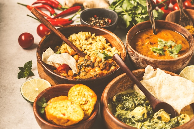 Даль, палак панир, карри, рис, чапати, чатни в деревянные чаши на белом столе.