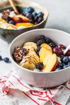 Овсянка с бананом, персиком, ягодами и суперпродуктами в мисках.