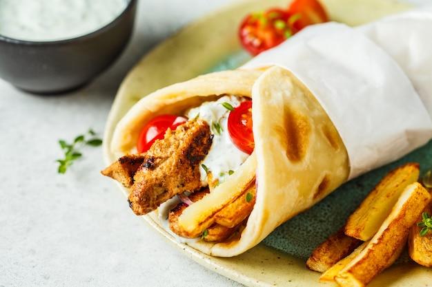 ジャイロスブラキは、鶏肉、ジャガイモ、ザジキソースを添えてピタパンに包みます。