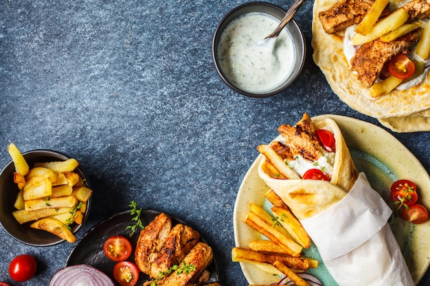 ジャイロスブラキは、鶏肉、ジャガイモ、ザジキソース、食材の背景とピタパンで包みます。