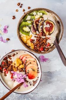 Смузи чаша с фруктами и мюсли с кокосовой раковиной чаши на сером фоне. здоровая веганская еда.