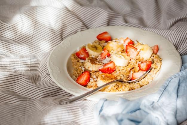 ベッドポグロムの白いプレートにバナナ、イチゴ、ピーナッツバターとオートミール。