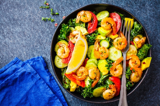 エビ、アボカド、青の背景、上面に黒い皿に野菜のサラダ。