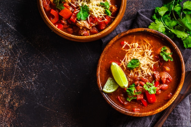 Традиционный мексиканский фасолевый суп с мясом и сыром в деревянной миске