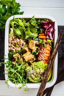 健康的なビーガンフード付きのランチボックス。米、さつまいも、豆腐、野菜が入った弁当箱。