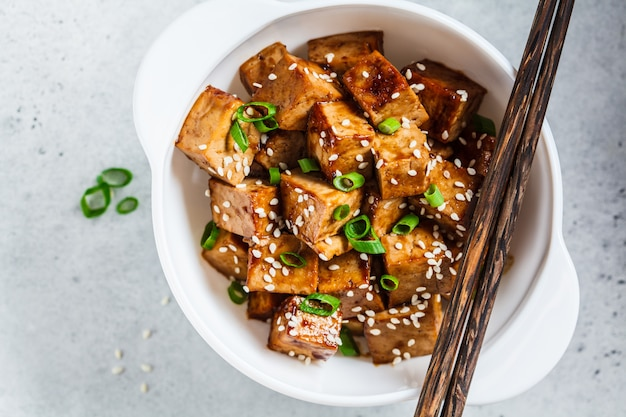 白いボウル、トップビューで照り焼きソースで揚げた豆腐。ビーガンフードコンセプト。
