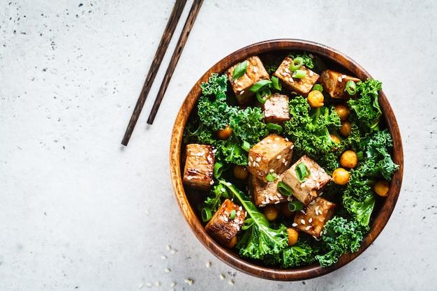 木製ボウル、コピースペース、トップビューでケールとひよこ豆の照り焼き豆腐サラダ。