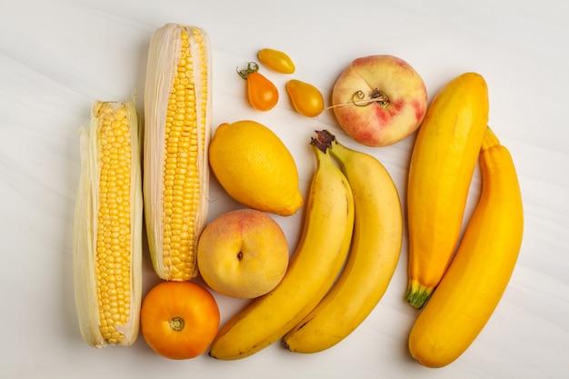 白い背景、上面に黄色の野菜の盛り合わせ。カロチンを含む果物と野菜。